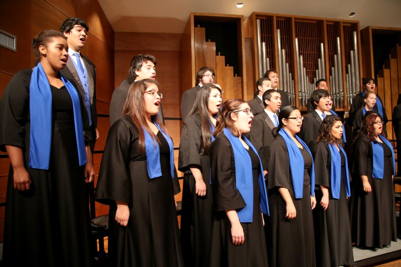 Students sing on stage in a recital hall.