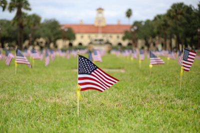 Rows of small American flags with yellow ribbons stand in front of the Javelina statue on Veterans Day at Texas A&M University-Kingsville.